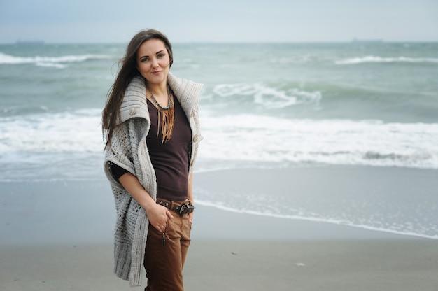Automne mode de vie portrait de jeune femme élégante hipster marchant sur une plage de la mer, vêtu d'une jolie tenue à la mode, profitez des week-ends et des voyages