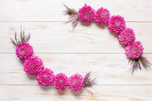 Automne motif floral avec des dahlias roses sur un fond en bois blanc.