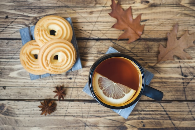 Automne nature morte avec une tasse de thé, des biscuits, un pull et des feuilles sur une surface en bois.