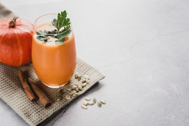 L'automne sain boit du jus de citrouille avec du persil et des graines de citrouille copiez l'espace
