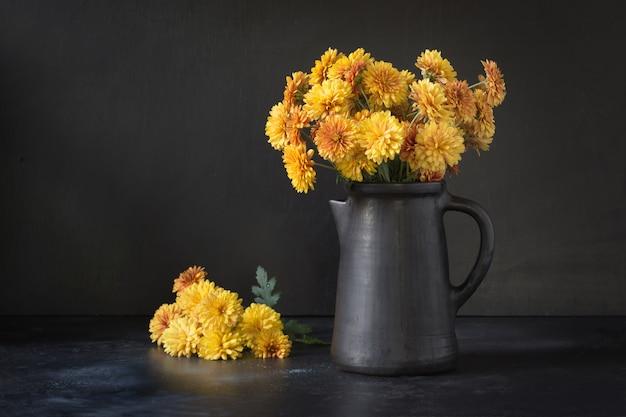 Automne sombre nature morte. tomber avec des fleurs de chrysanthème jaune dans un vase en terre cuite sur fond noir.