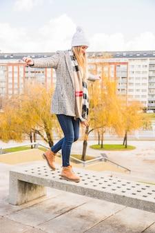 Automne vêtu femme équilibre banc de pierre
