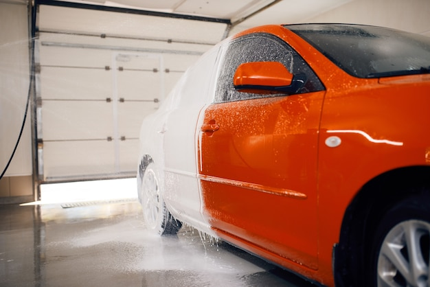 L'automobile est à moitié en mousse, service de lavage de voiture
