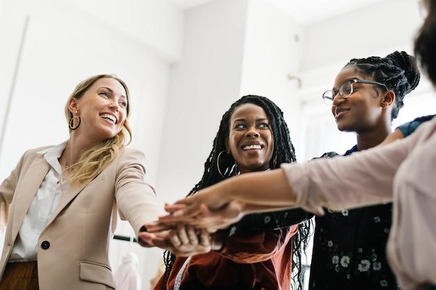 Autonomiser les femmes d'affaires empilant leurs mains