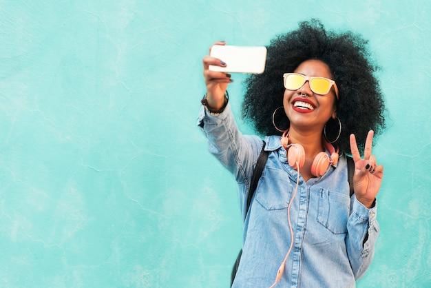 Autoportrait d'une belle jeune femme afro-américaine faisant un signe de paix. concept de selfie.