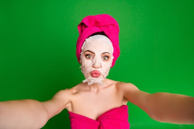 Autoportrait de belle jeune fille funky nue portant des lèvres de moue de thérapie de masque facial turban isolés sur fond de couleur vert clair
