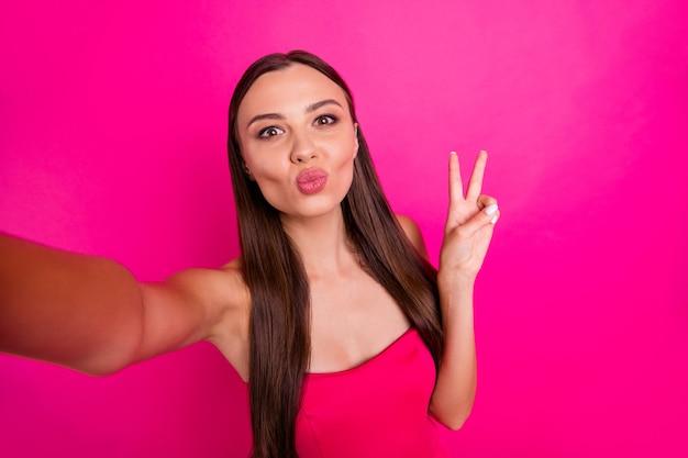 Autoportrait d'elle elle belle attrayante séduisante jolie jolie fille aux cheveux longs douce joyeuse envoi de baiser montrant v-sign isolé sur fond de couleur rose fuchsia brillant vif éclatant