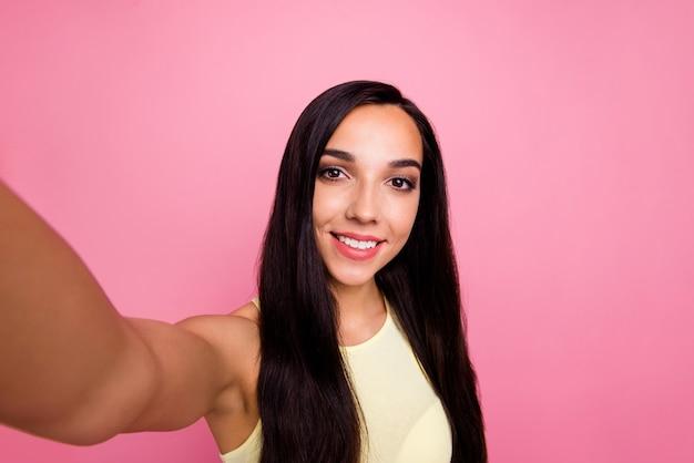 Autoportrait de fille isolée sur mur pastel rose