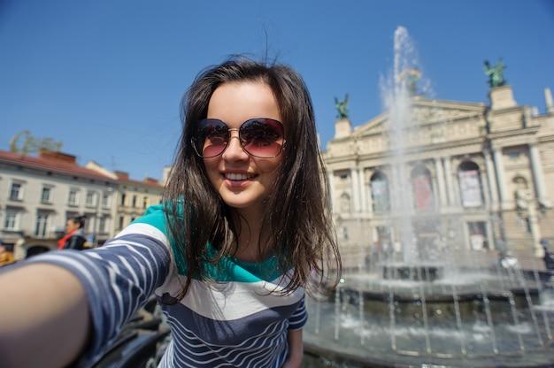 Autoportrait d'une jeune fille à lunettes dans la vieille ville