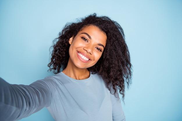 Autoportrait de joyeux bouclés ondulés positifs jolie jolie petite amie souriant à pleines dents portant un pull bleu prenant selfie fond de couleur pastel isolé