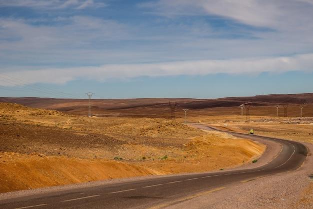 Autoroute entourée de collines sablonneuses avec centrales électriques