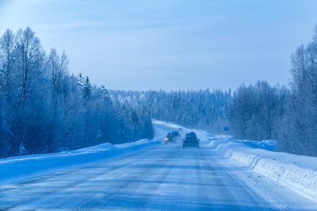 Autoroute à travers la forêt nordique d'hiver. plusieurs voitures