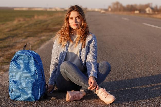 Une autostoppeuse sérieuse est assise les jambes croisées sur une route goudronnée avec son sac, aime voyager à la campagne, explore des endroits inconnus
