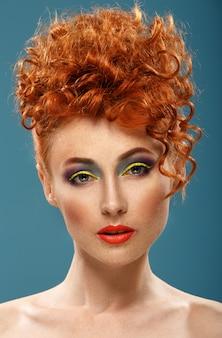Aux cheveux roux. belle fille avec un maquillage de couleur vive
