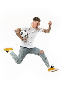 Avancez vers la victoire.le jeune homme en tant que joueur de football de football sautant et donnant des coups de pied dans le ballon au studio sur fond blanc. fan de football et concept de championnat du monde. s