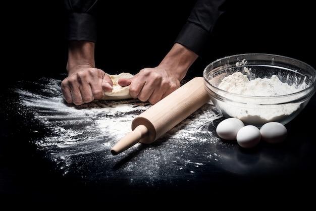 Avant la cuisson. gros plan des mains du jeune homme pétrir la pâte pendant la cuisson et le travail au restaurant.