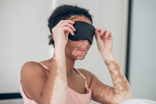 Avant de dormir. une jeune femme mettant un masque de sommeil