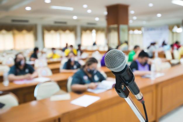 Avant du microphone avec arrière-plan flou de nombreuses personnes sur la salle. microphone sur scène. concept d'intérieur d'activité. concept de séminaire ou de réunion.