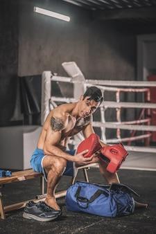 Avant l'entraînement. homme musclé assis dans un vestiaire dans une salle de sport
