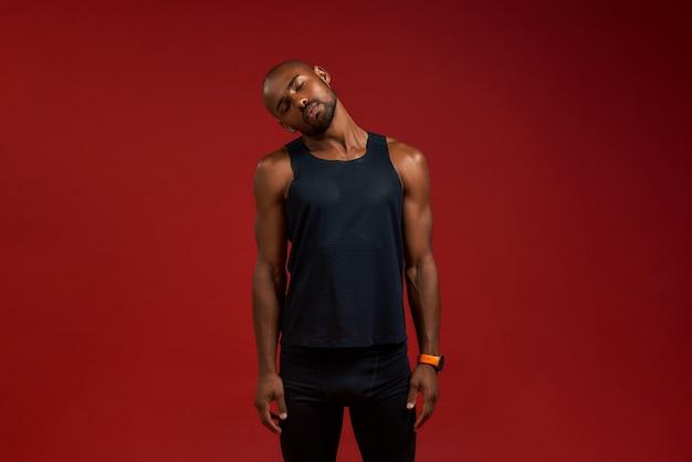 Avant l'entraînement, un jeune homme afro-américain fort en vêtements de sport s'échauffe en se tenant debout contre