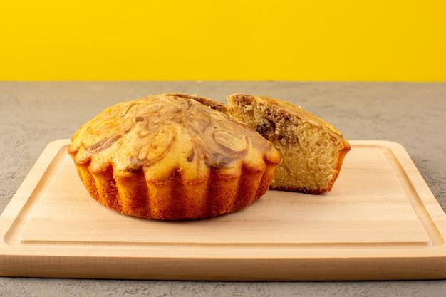 Un avant fermé vue gâteau sucré délicieux délicieux gâteau choco tranché sur le bureau carré de couleur crème