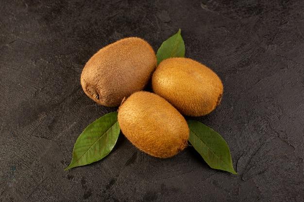 Un avant fermé vue kiwis bruns mûrs frais isolés juteux et fruits entiers avec des feuilles vertes