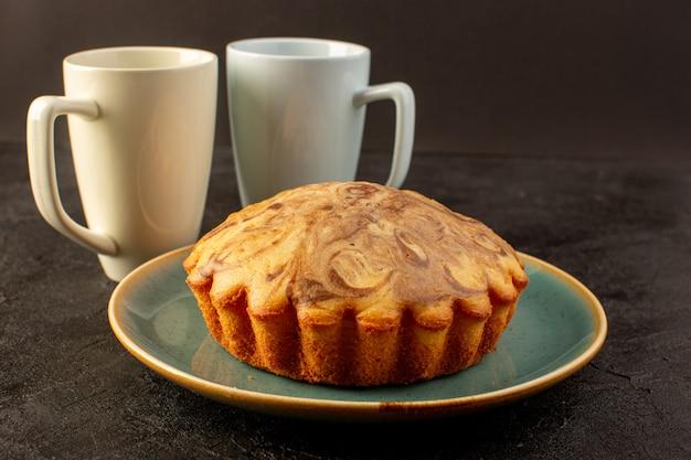 Un avant fermé vue ronde gâteau sucré délicieux délicieux gâteau au chocolat à l'intérieur de la plaque bleue avec paire de tasses blanches sur l'obscurité