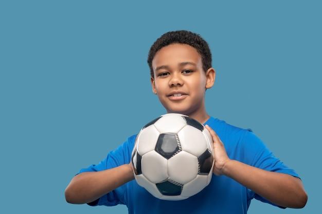 Avant de lancer. garçon souriant attentif à la peau foncée en t-shirt bleu de sport visant avec le ballon dans les mains en studio