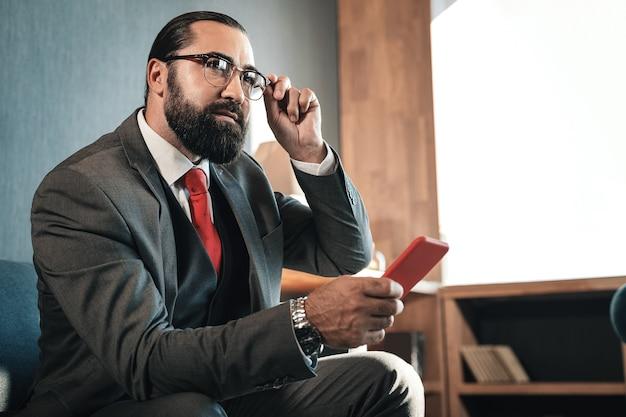 Avant négociation. homme d'affaires riche barbu aux cheveux noirs se sentant excité avant la négociation avec l'investisseur