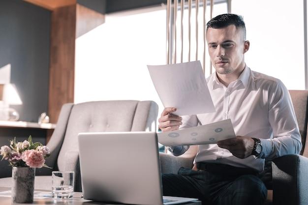 Avant la réunion. bel homme d'affaires se sentant très occupé tout en travaillant dur avant une réunion internationale