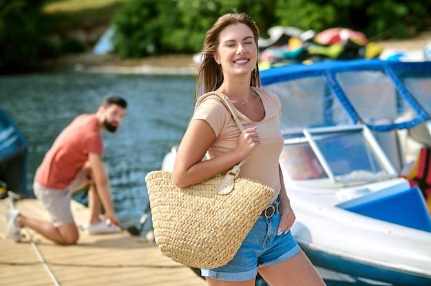 Avant une sortie en bateau. une jeune femme debout sur le quai pendant que son homme détachait le bateau
