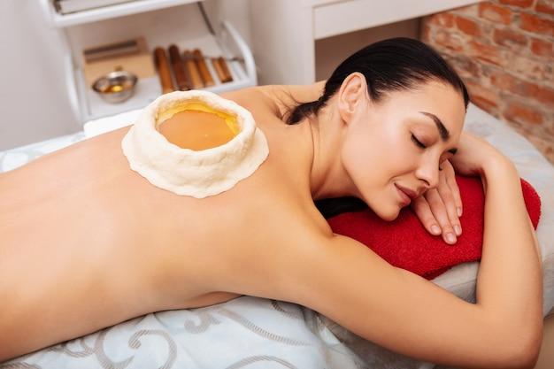 Avantages de la procédure. dame calme souriante allongée sur une serviette rouge dans une armoire spa avec piscine en argile pleine d'huile à l'arrière