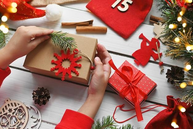 Avent joyeux noël un enfant tient une boîte cadeau en papier kraft à côté d'autres surprises dans des sacs