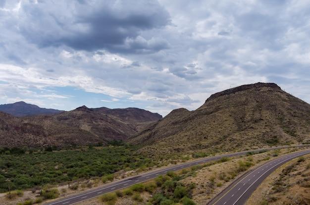 Aventure de vue aérienne voyageant sur la route du désert sur l'autoroute asphaltée à travers les montagnes arides du désert de l'arizona