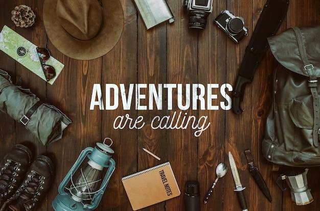 Les aventures appellent texte, message, lettrage. cadre d'équipement de randonnée comprenant machette, couteau, vêtements, bottes, lanterne, bloc-notes, chapeau, carte, boussole. carte postale wanderlust, affiche, bannière.