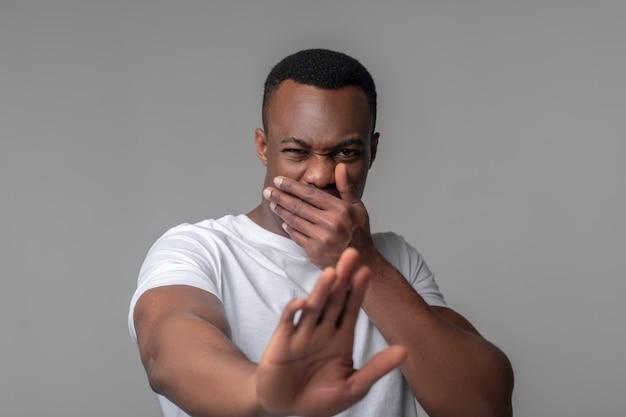 Aversion, émotion. jeune adulte homme à la peau sombre avec grimace couvrant sa bouche avec des gestes de la main en repoussant en studio photo