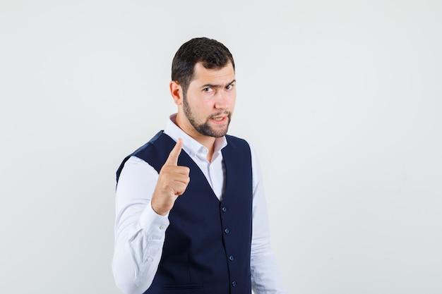 Avertissement de jeune homme avec le doigt en chemise et gilet et à la stricte