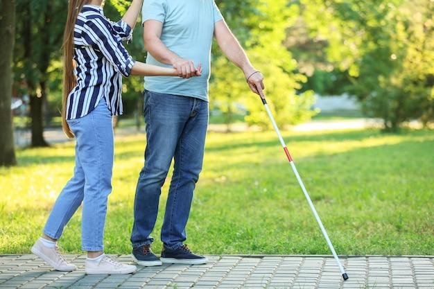 Aveugle homme mûr avec sa fille marchant dans le parc