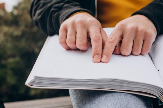 Aveugle lisant en touchant le livre en braille