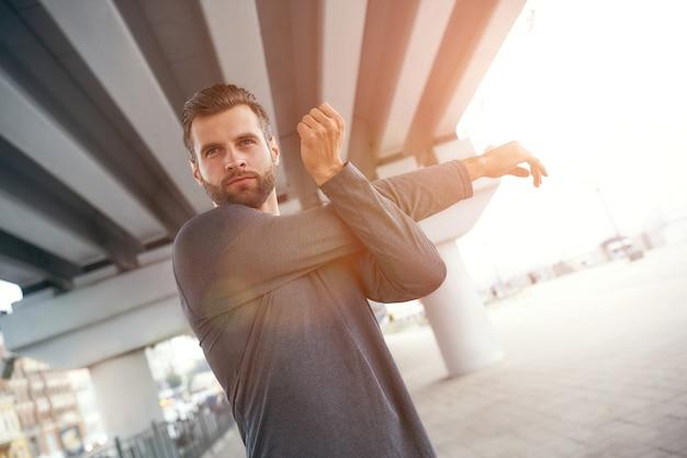 Avez-vous fait de l'exercice aujourd'hui portrait d'un jeune homme barbu en tenue de sport étirant son bras tout en