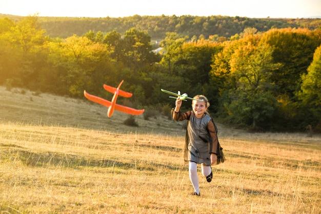 Aviateur pilote enfant avec avion rêve de voyager en été dans la nature au coucher du soleil les enfants courir joyeusement ensemble pendant le beau temps ensoleillé dans le parc