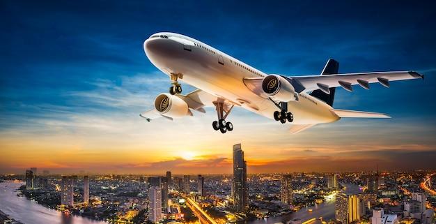 Avion d'affaires prend le dessus sur le paysage urbain sur beau coucher de soleil