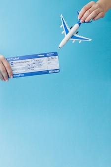 Avion et billet d'avion en main de femme sur fond bleu. concept de voyage, espace copie
