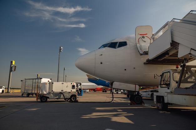 Avion blanc à l'aéroport faisant le plein à l'extérieur pendant la journée. détails de l'avion. avion, expédition, concept de transport