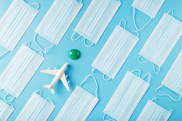 Un avion blanc entouré de masques de protection sur une surface bleue avec un point vert comme