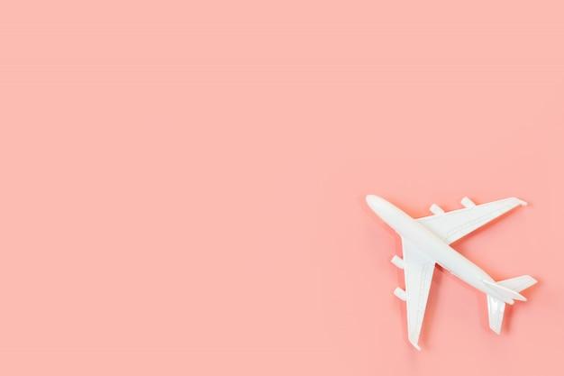 Avion blanc sur fond rose