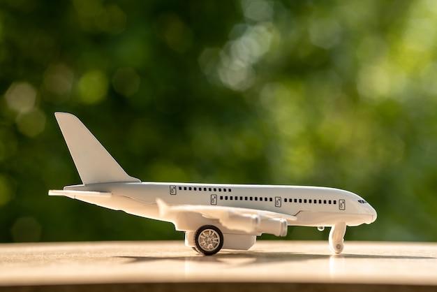 Avion blanc jouet. l'été se dresse sur un fond en bois blanc. fermer.