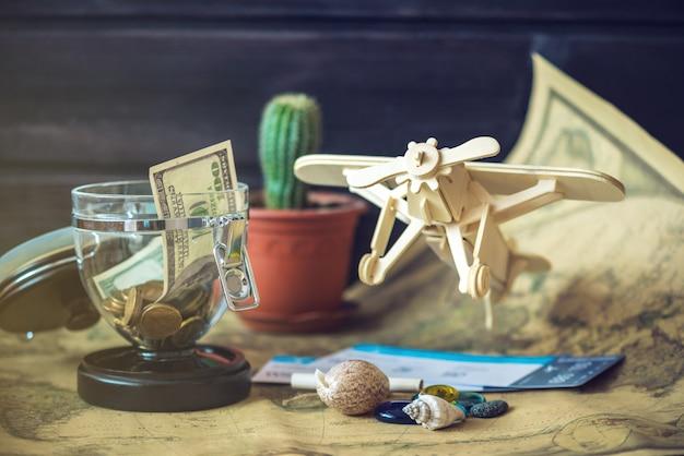 Avion en bois jouet sur une carte du monde avec des pierres colorées et des coquillages de la mer dans un style rétro.