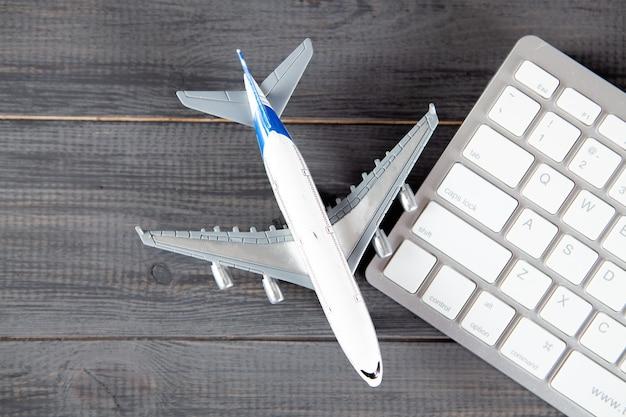 Avion et clavier. achat en ligne de billets d'avion sur une table en bois gris