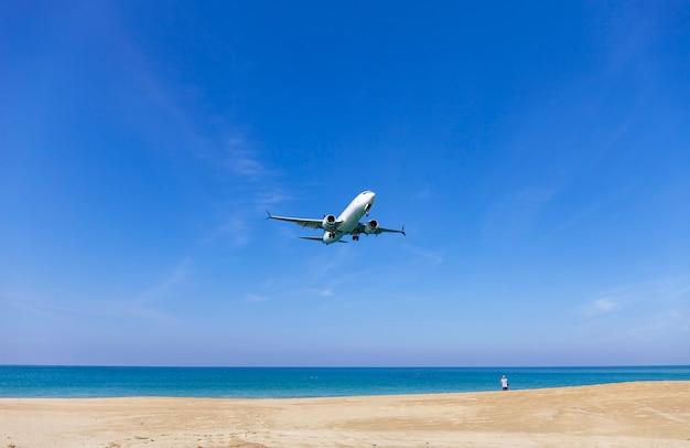 Avion commercial atterrissant au-dessus de la mer et le ciel bleu clair